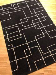 Schwarzer Teppich mit beige-farbenem Muster